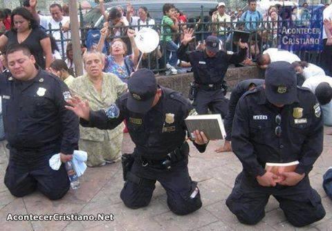 Policías oran de rodillas en la calle